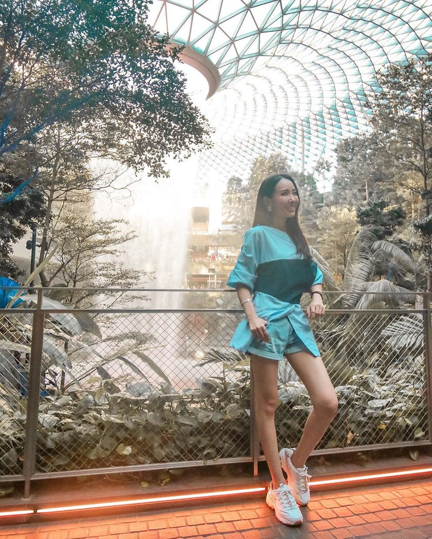 A photo of a girl posing in front of an artificial waterfall